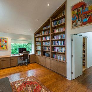 Immagine di uno studio moderno di medie dimensioni con libreria, pareti bianche, pavimento in legno massello medio, camino classico, cornice del camino in pietra, scrivania incassata e pavimento marrone
