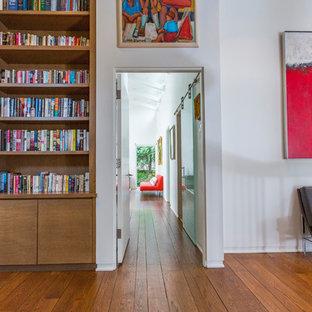 シンシナティの中くらいのモダンスタイルのおしゃれなホームオフィス・書斎 (ライブラリー、白い壁、無垢フローリング、標準型暖炉、石材の暖炉まわり、造り付け机、茶色い床) の写真