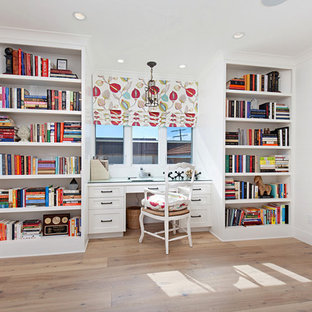 Large transitional built-in desk medium tone wood floor home office library photo in Orange County with white walls