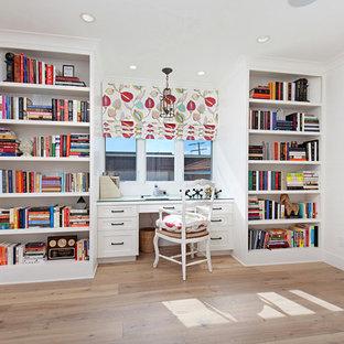 Стильный дизайн: большой кабинет в стиле современная классика с библиотекой, белыми стенами, паркетным полом среднего тона и встроенным рабочим столом - последний тренд