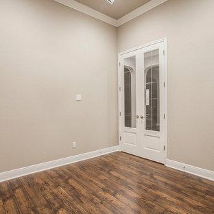 オースティンの大きい地中海スタイルのおしゃれな書斎 (ベージュの壁、ラミネートの床、暖炉なし、茶色い床) の写真