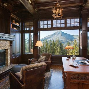 Klassisches Arbeitszimmer mit dunklem Holzboden, Kamin, Kaminsims aus Stein und freistehendem Schreibtisch in Sonstige