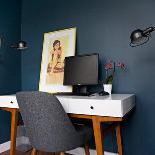 Immagine di un piccolo studio minimalista con pareti blu, pavimento in legno massello medio, camino classico, cornice del camino in pietra e scrivania autoportante