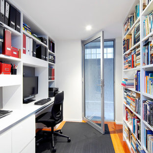 Photo of a small contemporary study in Sydney with white walls, medium hardwood flooring, a built-in desk and brown floors.