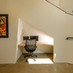 Immagine di un piccolo ufficio minimal con scrivania incassata, pareti bianche, pavimento in cemento e nessun camino