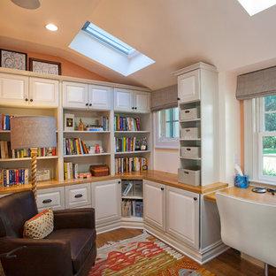 Foto di un piccolo ufficio country con pareti arancioni, pavimento in legno massello medio, nessun camino e scrivania incassata