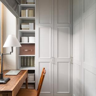На фото: рабочее место в стиле современная классика с серыми стенами, светлым паркетным полом, отдельно стоящим рабочим столом и бежевым полом