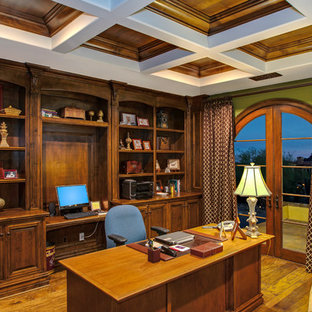 Example of a large classic built-in desk medium tone wood floor study room design in Phoenix with green walls and no fireplace