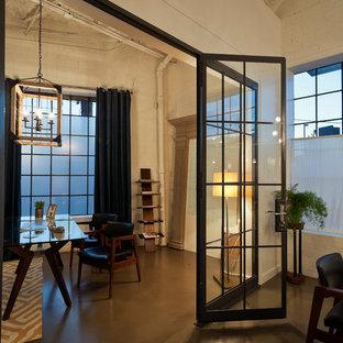 Ejemplo de despacho actual, grande, sin chimenea, con paredes blancas, suelo de cemento, escritorio independiente y suelo gris