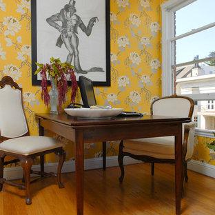 Imagen de despacho ecléctico con paredes amarillas