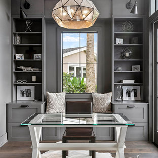 オーランドの中くらいのトランジショナルスタイルのおしゃれな書斎 (自立型机、茶色い床、グレーの壁、濃色無垢フローリング) の写真