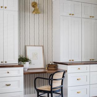 Immagine di un piccolo ufficio american style con pareti beige, pavimento in legno massello medio, camino classico, cornice del camino in legno, scrivania incassata e pavimento marrone