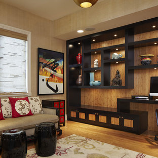 This is an example of a mid-sized asian home office in Miami with medium hardwood floors, a built-in desk, beige walls and no fireplace.