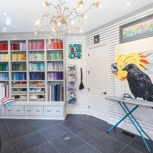 アトランタの広いトランジショナルスタイルのおしゃれなクラフトルーム (白い壁、磁器タイルの床、造り付け机、黒い床、パネル壁) の写真