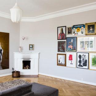 他の地域の広いトランジショナルスタイルのおしゃれなホームオフィス・書斎 (グレーの壁、コーナー設置型暖炉、ライブラリー、淡色無垢フローリング、木材の暖炉まわり、自立型机、茶色い床) の写真