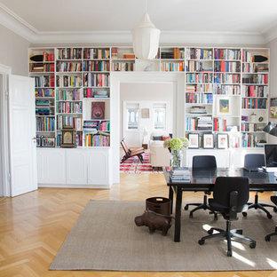 Diseño de despacho clásico renovado, grande, con paredes grises, suelo de madera clara, escritorio independiente, suelo marrón, chimenea de esquina y marco de chimenea de madera