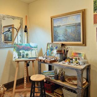 На фото: домашняя мастерская в средиземноморском стиле с бежевыми стенами, полом из терракотовой плитки и отдельно стоящим рабочим столом без камина с