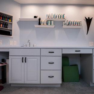 Esempio di una grande stanza da lavoro minimalista con pareti blu, scrivania incassata, pavimento in ardesia, nessun camino e pavimento grigio