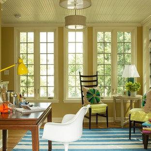 Esempio di uno studio boho chic con pareti gialle, pavimento in legno massello medio e scrivania autoportante