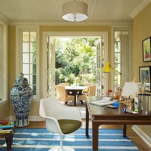 Стильный дизайн: кабинет в стиле фьюжн с желтыми стенами, паркетным полом среднего тона и отдельно стоящим рабочим столом - последний тренд