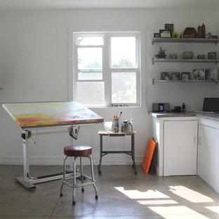 Ispirazione per un piccolo atelier industriale con pareti bianche, nessun camino, scrivania autoportante e pavimento in cemento