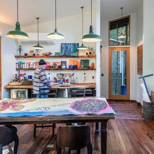 Imagen de estudio bohemio con paredes blancas, suelo de madera oscura, escritorio empotrado y suelo marrón