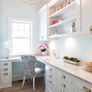 Maritimes Arbeitszimmer mit Arbeitsplatz, blauer Wandfarbe, hellem Holzboden und Einbau-Schreibtisch in Minneapolis
