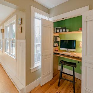 Modelo de despacho de estilo de casa de campo, pequeño, con paredes verdes, escritorio empotrado, suelo marrón y suelo de madera en tonos medios