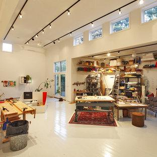 Cette image montre un très grand bureau minimaliste de type studio avec un mur blanc, un sol en bois peint et un sol blanc.