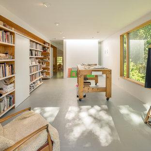 Idée de décoration pour un bureau design de taille moyenne et de type studio avec un mur blanc, un poêle à bois, un manteau de cheminée en métal, un bureau indépendant, un sol gris et béton au sol.