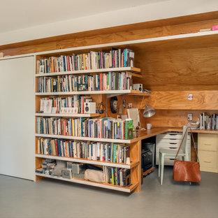 Immagine di un piccolo studio design con libreria, pareti multicolore, scrivania incassata, pavimento grigio e pavimento in cemento