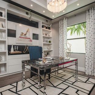 Стильный дизайн: рабочее место в современном стиле с серыми стенами, отдельно стоящим рабочим столом, многоуровневым потолком, темным паркетным полом и коричневым полом без камина - последний тренд