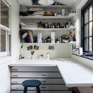 Foto di una piccola stanza da lavoro industriale con pareti bianche, pavimento in pietra calcarea, nessun camino, scrivania incassata e pavimento grigio