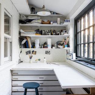 Cette photo montre un petit bureau atelier industriel avec un mur blanc, un sol en calcaire, aucune cheminée, un bureau intégré et un sol gris.
