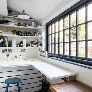 Exempel på ett litet industriellt hobbyrum, med vita väggar, kalkstensgolv, ett inbyggt skrivbord och grått golv