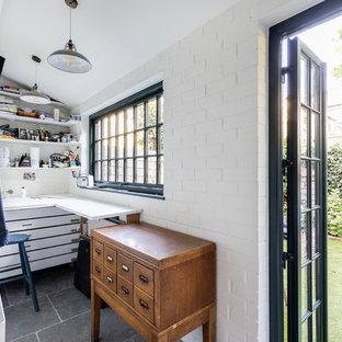 Foto de sala de manualidades industrial, pequeña, sin chimenea, con paredes blancas, suelo de piedra caliza, escritorio empotrado y suelo gris
