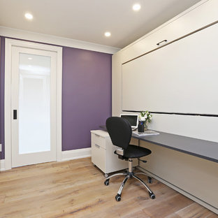 This is an example of a classic home office and library in Toronto with purple walls, light hardwood flooring, no fireplace and a built-in desk.