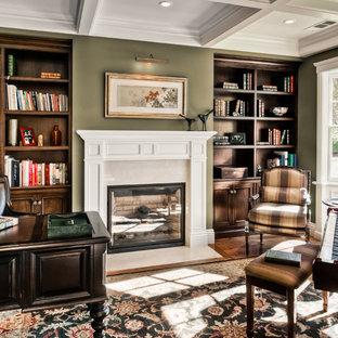 Inredning av ett klassiskt mellanstort hemmabibliotek, med gröna väggar, mörkt trägolv, en standard öppen spis, en spiselkrans i gips och ett fristående skrivbord