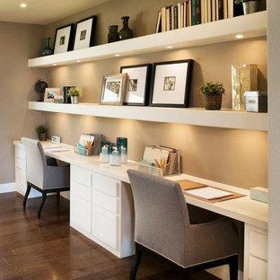 Modelo de despacho actual, de tamaño medio, con paredes beige, suelo de madera oscura y escritorio empotrado