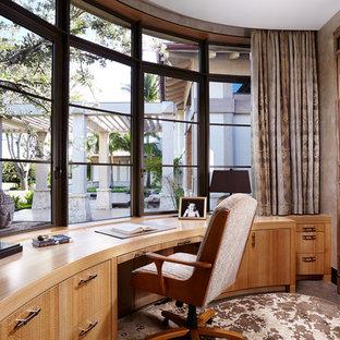 Idéer för att renovera ett mellanstort orientaliskt hemmabibliotek, med beige väggar, ett inbyggt skrivbord, betonggolv och brunt golv