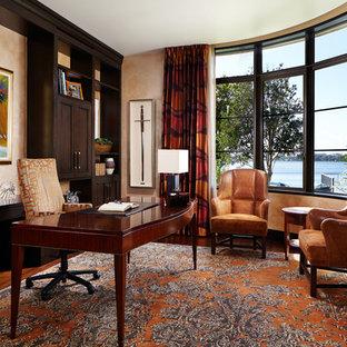 Inspiration för stora asiatiska hemmabibliotek, med beige väggar, ett fristående skrivbord, mörkt trägolv och brunt golv