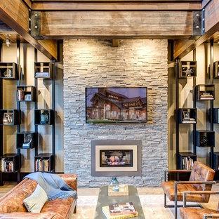 Foto de despacho tradicional renovado, grande, con chimeneas suspendidas, marco de chimenea de piedra y suelo de madera en tonos medios