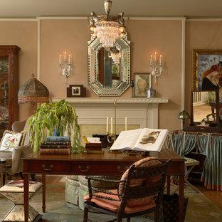 Inredning av ett klassiskt hemmabibliotek, med mellanmörkt trägolv, ett fristående skrivbord, en standard öppen spis, rosa väggar och en spiselkrans i trä