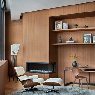 Idéer för att renovera ett funkis arbetsrum, med bruna väggar, mellanmörkt trägolv, en bred öppen spis, ett fristående skrivbord och brunt golv