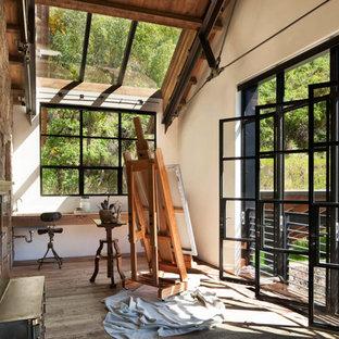 Foto di una stanza da lavoro rustica con pareti bianche, pavimento in legno massello medio, scrivania incassata e pavimento marrone