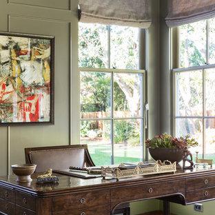 Inredning av ett klassiskt mellanstort hemmabibliotek, med gröna väggar, mörkt trägolv, ett fristående skrivbord och brunt golv
