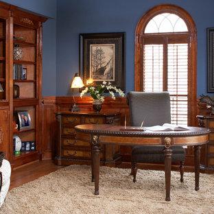 Idéer för mellanstora vintage hemmabibliotek, med blå väggar, mellanmörkt trägolv och ett fristående skrivbord