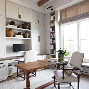 Klassisches Arbeitszimmer mit weißer Wandfarbe, dunklem Holzboden, freistehendem Schreibtisch, braunem Boden und freigelegten Dachbalken in Austin