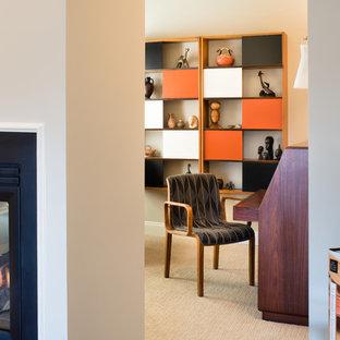 Diseño de despacho retro, pequeño, con moqueta, chimenea de doble cara y escritorio independiente