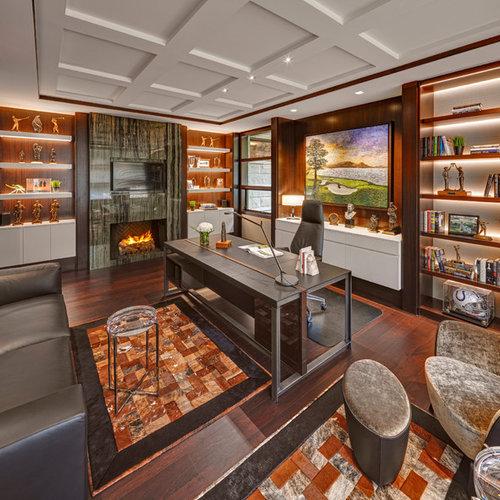 Modernes Arbeitszimmer Mit Kamin, Dunklem Holzboden, Kaminsims Aus Stein,  Freistehendem Schreibtisch Und Braunem